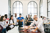 """ROME, ITALY - 15 OCTOBER 2018: Cristian (right), a leather artisan working for FENDI, explains the leather bags production process to students during the LVMH Journées Particulières exhibition at the Fendi headquarters in Rome, Italy, on October 15th 2018.<br /> <br /> The LVMH Journées Particulières is is a series of exhibitions that show the creations and history of the LVMH fashion houses. The driving theme behind the Journées Particulières is to allow the general public to discover the inner workings of the Houses which are part of the LVMH heritage.The LVMH Journées Particulières exhibition by fashion house FENDI takes place at their headquarters at the Palazzo della Civiltà Italiana, also called the """"Colosseo Quadrato"""" (Square Colosseum),  an outstanding jewel of the 20th century Roman architecture."""