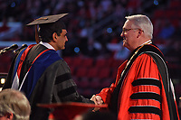 Chancellor Randy Woodson congratulates a doctoral grad at 2017 Winter Commencement in PNC Arena.
