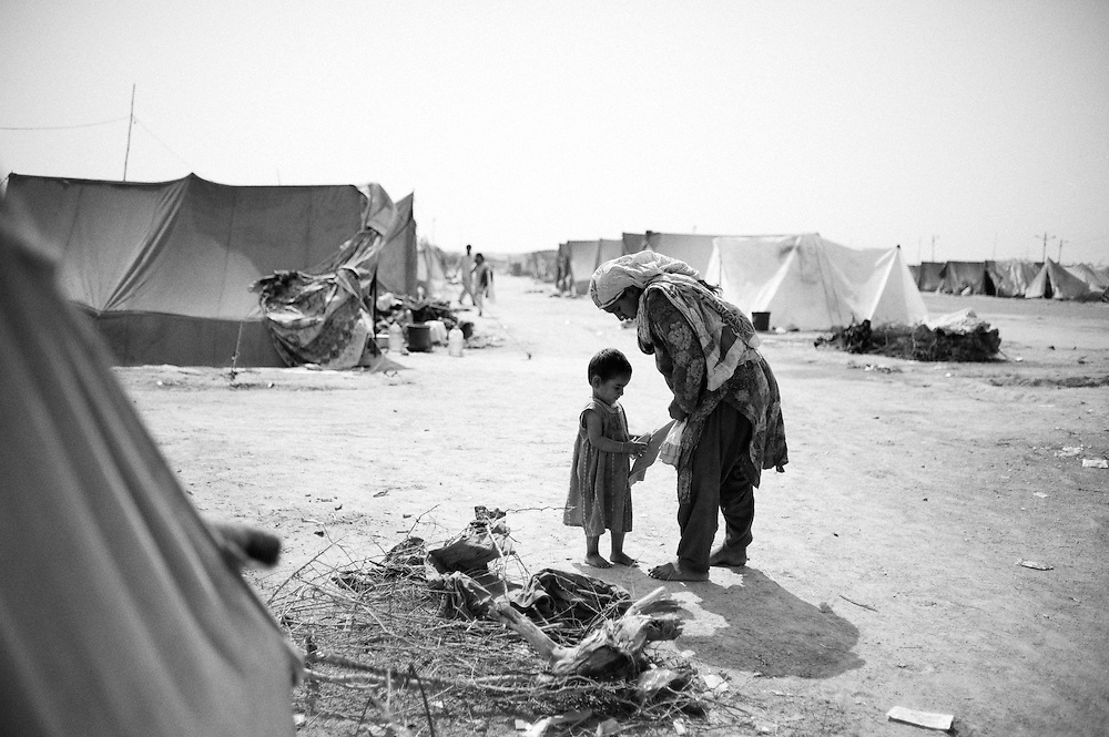 Hamida changes Mehmooda's clothes outside the tent. After washing the clothes are put out to dry on the collected firewood. Karachi, Pakistan, 2010