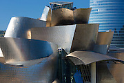Architect Frank Gehry's Guggenheim Museum futuristic design in titanium and glass and Iberdrola Tower behind at Bilbao, Spain