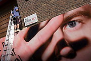 A giant eye from a construction site hoarding watches street next to a workman up a ladder on Neal Street, London.