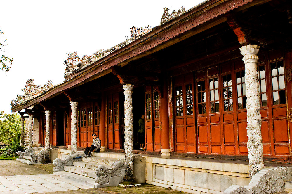 Exterior of a hall in the compound.  A visitor (man) sits on the steps putting on his shoes.  The carved wooden doors are fronted by carved marble columns.