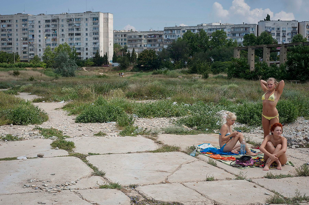 Three young women sunbathe at the edge of a run down Soviet era housing estate by the Black Sea (out of the picture).<br />