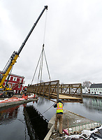 The crane and ground crew guides a metal footbridge in place at Perley Canal and Jewett Brook behind Church Street on Thursday morning.  (Karen Bobotas/for the Laconia Daily Sun)