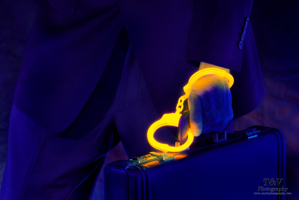 A businessman linked to his suitcase with glowing golden handcuffs.Black light