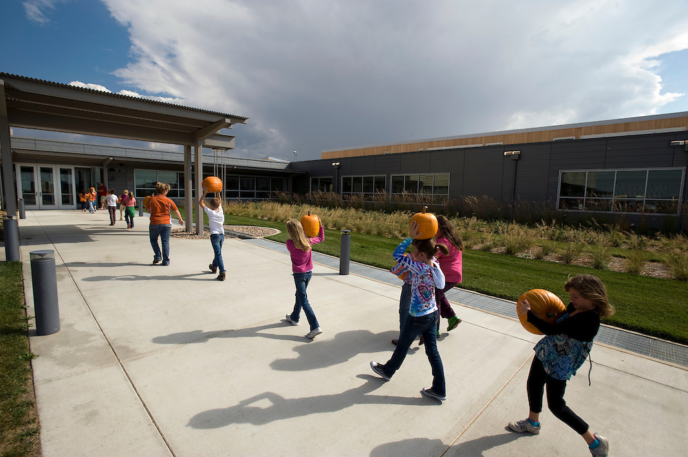 "Greensburg, Kansas, USA..K-12 School Facility, Kiowa County School (children getting their pumpkins for halloween)...The (K-12) school facility is designed to support Greensburg's newly adopted master plan and vision to be a model ""eco-community"". The school campus is being designed to LEED for Schools Platinum standards. With the advent of the 2010 school year, the campus welcomes students from throughout Kiowa County...""Greensburg: Better, Stronger, Greener!"".On May 4, 2007, an EF5 tornado cut a 1.7-mile path of destruction through Greensburg, Kansas. Winds reaching speeds of 205 miles per hour uprooted trees, demolished homes and leveled the town. Eleven people died and 95% of the buildings were destroyed beyond repair. Residents have since worked furiously to rebuild it in a way that is both economically and environmentally sustainable and to meet the highest environmental standards. Greensburg, whose population has dropped from about 1400 to 800 following the storm and is now growing again, is currently the greenest town in America and the first in the United States to pass a resolution to certify that all city-owned buildings earn LEED Platinum accreditation, the highest level of the LEED rating system...Photo © Stefan Falke"