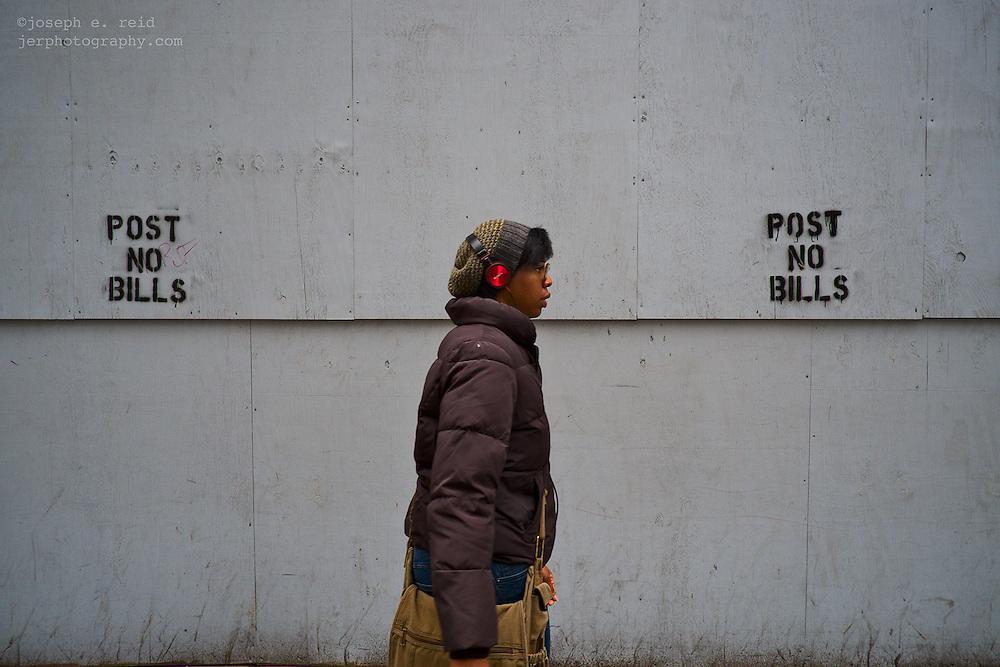 """Woman walking past """"post no bills"""" signs, New York, NY, US"""