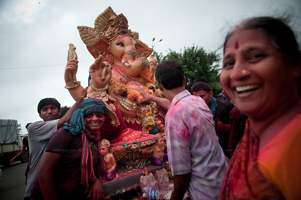 An Indian family carry their idol of Ganesh for immersion in the Indian ocean on the last day of the Ganesh Chaturthi festival. Ganesh, the elephant-headed son of Shiva and Parvati is widely worshiped as the supreme God of wisdom, prosperity and good fortune. Mumbai, September 2009.