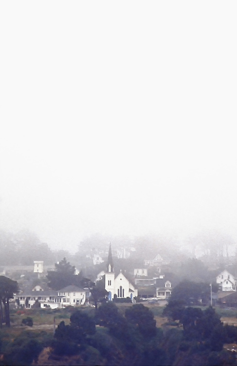 Foggy and gray view toward Main Street in Mendocino, California. The Presbyterian church with its landmark steeple, built of redwood in 1868.