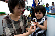 Junko Nakahodo and her daughter Ai, volunteers participating in the Team Tyura Sango coral reef restoration project, attach pieces of coral to ceramic name tags that are placed into coral nurturing tanks before being bolted to the sea bed in the nearby bay in Onna Village, Okinawa Prefecture, Japan, on Saturday, June 23, 2012.  Coral seedlings are put on small plates made of coral-like components, then fixed in place by wire and given a registration  number. They are raised at an aquafarm for several months before being bolted to the sea floor. Photographer: Robert Gilhooly