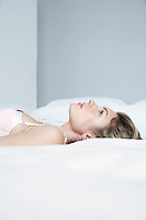 Profile of young woman in underwear lying on bed close-up