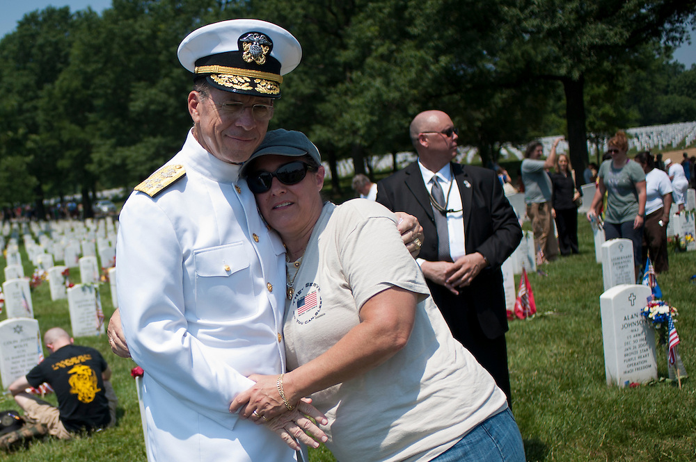 HELENE PACI, of Bethesda, MD, hugs Chairman of the Joint Chiefs of Staff Admiral MIKE MULLEN during his visit to Section 60 at Arlington National Cemetery on Memorial Day.