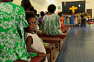 Young Ni Vanuatu girl next to her mother in a church. Christianity is the dominant religion in Vanuatu and church is a major part of the population's every day life. Village of Wintua South West Bay, Malekula, Vanuatu