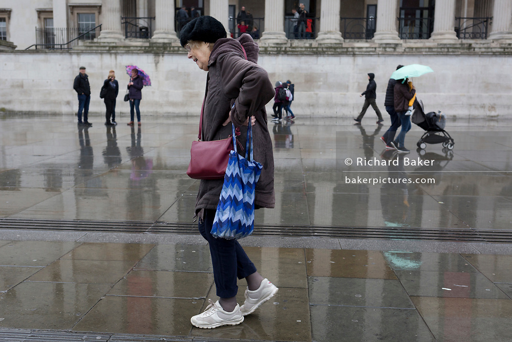 An elderly pedestrian walks painfully past the architecture of the National Gallery in Trafalgar Square, Westminster, on 9th April 2019, in London, England.