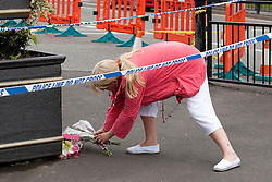 © Licensed to London News Pictures. 27/06/2012. Oldham , UK . A large explosion , believed to be caused by gas , has brought down at least one house in an Oldham terrace. A woman lays flowers alongside other tributes at the scene . Photo credit : Joel Goodman/LNP