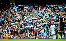Manchester City fans in the stands hold up scarves during the Premier League match at the Etihad Stadium, Manchester.
