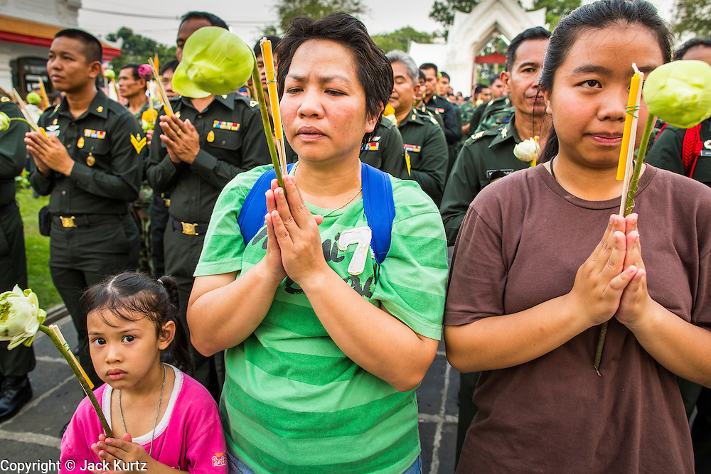"""25 FEBRUARY 2013 - BANGKOK, THAILAND:   A Thai family prays in front of Wat Benchamabophit Dusitvanaram (popularly known as either Wat Bencha or the Marble Temple) on Makha Bucha Day. Makha Bucha is a Buddhist holiday celebrated in Myanmar (Burma), Thailand, Cambodia and Laos on the full moon day of the third lunar month (February 25 in 2013). The third lunar month is known in Thai is Makha. Bucha is a Thai word meaning """"to venerate"""" or """"to honor"""". Makha Bucha Day is for the veneration of Buddha and his teachings on the full moon day of the third lunar month. Makha Bucha Day marks the day that 1,250 Arahata spontaneously came to see the Buddha. The Buddha in turn laid down the principles his teachings. In Thailand, this teaching has been dubbed the 'Heart of Buddhism'.    PHOTO BY JACK KURTZ"""