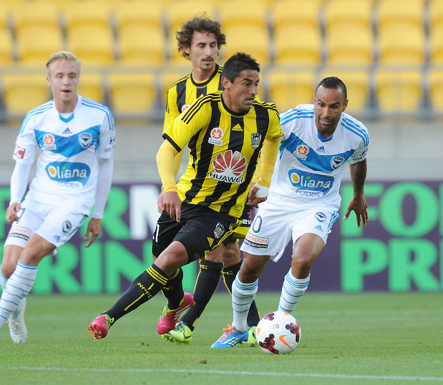 Phoenix's Carlos Hernandez turns in front of Melbourne Victory's Archie Thompson in the A-League football match at Westpac Stadium, Wellington, New Zealand, Saturday, Januray 18, 2014. Credit:SNPA / Ross Setford