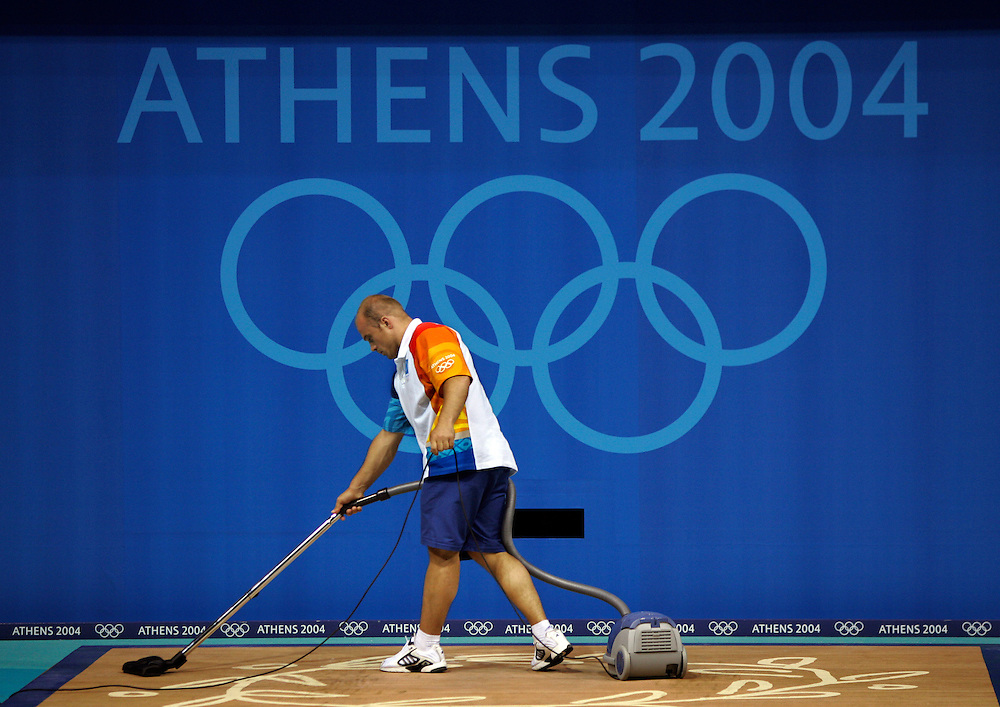 An Olympic volunteer vacuumed the weightlifting mat between snatch and clean and jerk portions in the Olympic weightlifting event at Nikaia Olympic Weightlifting Hall in Athens, Greece.