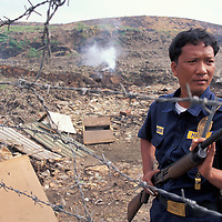Philippines, Luzon Island, Panfilo Arranchado is armed guard at Manila's Smokey Mountain garbage dump