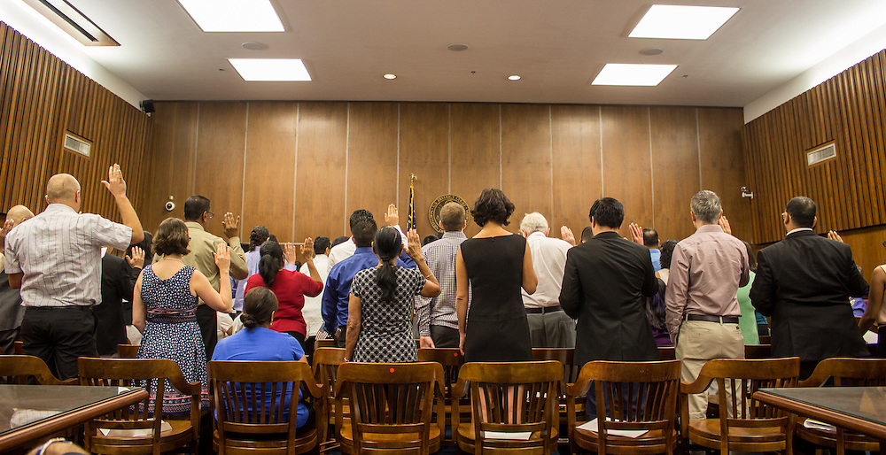 Recently naturalized U.S. citizens take an oath during the naturalization ceremony at the U.S. District Court Clerk in downtown Gainesville  Thursday morning. (photo by Samuel Navarro)