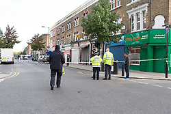 © Licensed to London News Pictures. 27/09/2015. London, UK. Police officers and a local resident at the cordon on Chatsworth Road next to Regal Pharmacy. Police have launched a murder investigation after a man was shot dead in the street outside Regal Pharmacy next to Mighty Meats butcher shop in Chatsworth Road, Hackney, east London yesterday. Photo credit : Vickie Flores/LNP