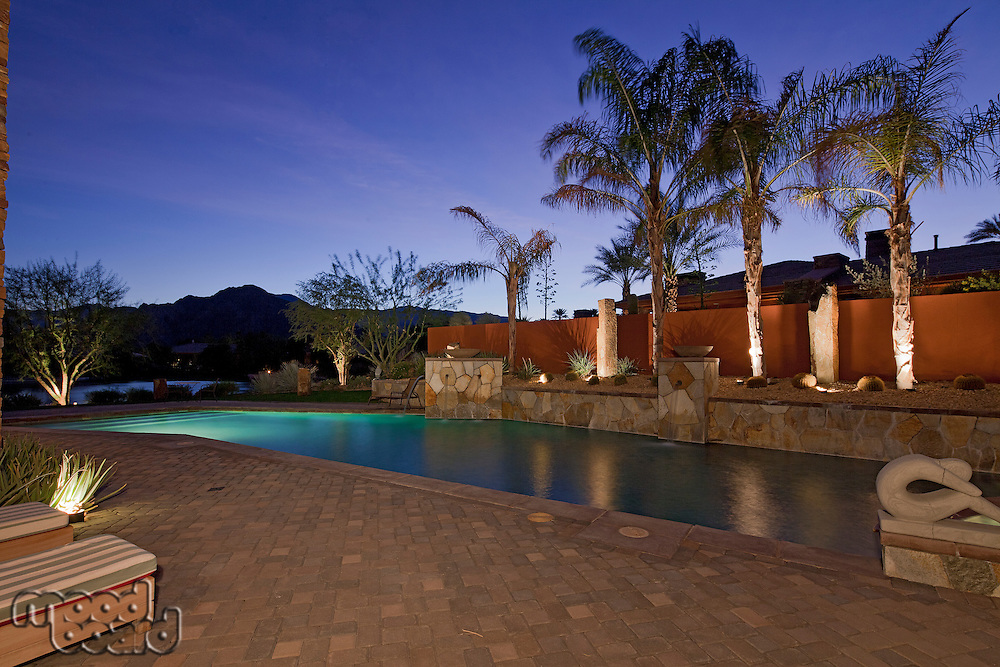 Swimming pool under lights in evening of luxury mansion