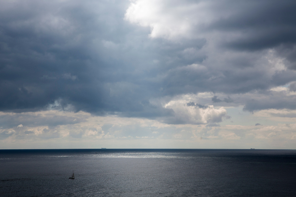 A sail boat sails across the tranquil waters of The English Chanel in the forefront, and two large shipping containers sail along the horizon line as seen from Folkestone, Kent, England, United Kingdom. The sky is full with moody dark and light white stratocumulus clouds (photo by Andrew Aitchison / In pictures via Getty Images)