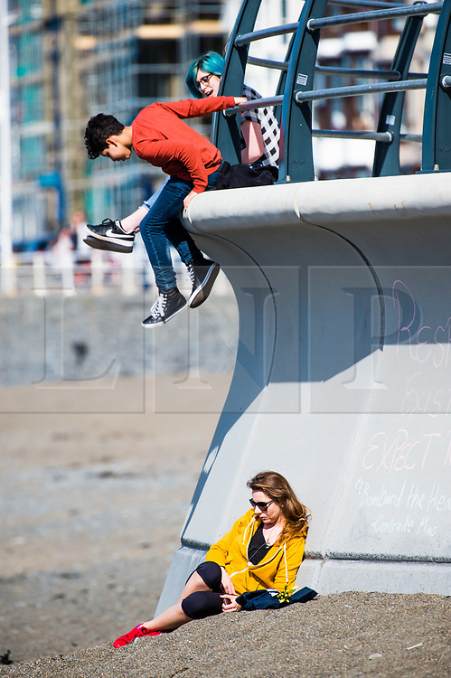 © London news pictures. 25/03/2017. Aberystwyth, UK.<br /> People on the beach on an afternoon of glorious sunshine and clear blue skies in Aberystwyth on the west wales coast, with temperatures expected to reach 18 or 19ºc by the afternoon. Sheltered from the cooling effects of an easterly wind, West Wales is expected to be the warmest pace in the UK today (Sat). Photo credit: Keith Morris/LNP