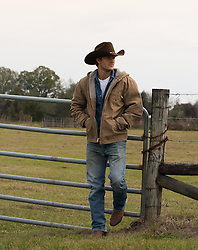 shirtless hunky cowboy in the rain on a ranch cowboy leaning on a gate at a ranch