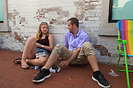 Huntington, New York, U.S. - August 6, 2014 - A young woman and man sit on the sidewalk while waiting on line to attend the book signing for Hillary Clinton's new memoir, Hard Choices, at the Book Revue in Huntington, Long Island. Clinton's book is about her four years as America's 67th Secretary of State and how they influence her view of the future.