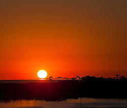 A gorgeous sunset along the Gulf Coast of Destin Florida with a fisherman in the foreground.