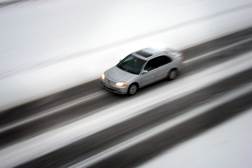JEROME A. POLLOS/Press..A car travels along the eastbound lane of Interstate-90 Thursday in between tire tracks, snow and ice.