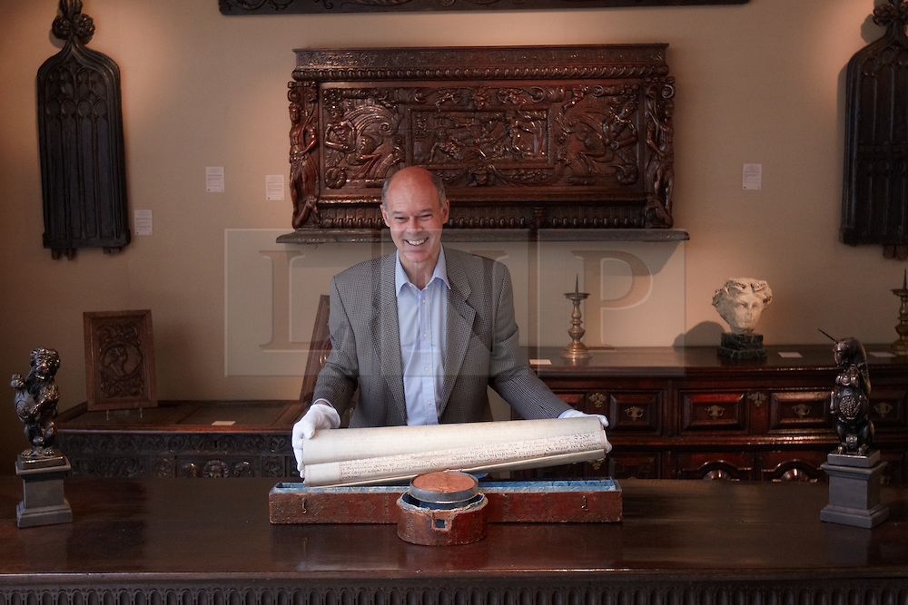 © licensed to London News Pictures. LONDON, UK  08/06/2011. Dealer Paul Beedham examines a legal document from 1711, valued at £40,000, complete with leather case and seal at the Olympia International Fine Art & Antiques Fair. All 30,000 items on sale from 150 dealers are vetted for authenticity by a panel of experts. The show opens in Olympia tomorrow (Thursday) and runs for 11 days. Please see special instructions for usage rates. Photo credit should read CLIFF HIDE/LNP