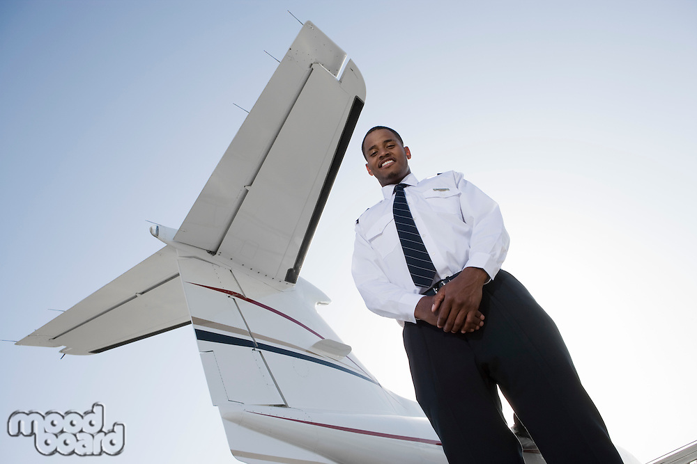 Portrait of flight attendant standing in front of private jet.