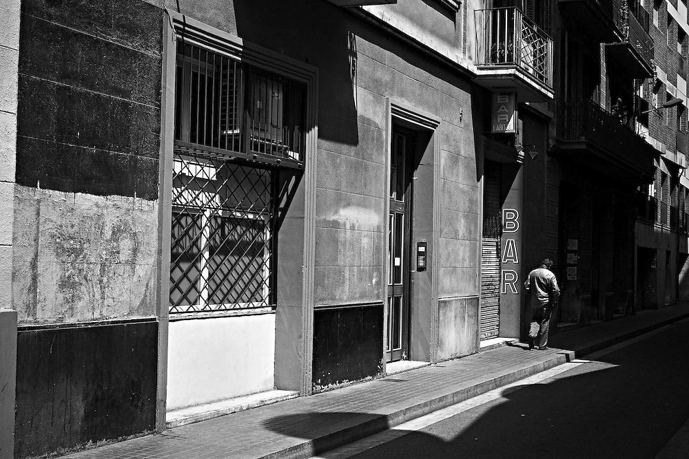 Man walking past closed bar, Gracia district, Barcelona