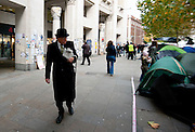 A man dressed in a Bowler hat and suit passes the Occupy London protest outside St Pauls Cathedral in Central London on October 31st 2011..The Dean of St. Paul's Cathedral in London on Monday became the second high-profile clergy member to step down amid mounting controversy over anti-capitalist protests on the church's grounds.
