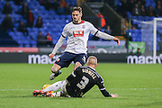 Brentford defender Jake Bidwell  and Bolton Wanderers defender Dorian Dervite  challenge for the ball during the Sky Bet Championship match between Bolton Wanderers and Brentford at the Macron Stadium, Bolton, England on 30 November 2015. Photo by Simon Davies.