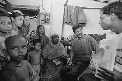 BANGLADESH TONGI ERSHAD COLONY 13OCT00 - Our interpreter, Khaleq (R), explains our cause to the mother of another child living in the Netherlands, Rashida. In the past, several Dutch-Bangladeshi children (now adults) have visited the Ershad colony and by a freak accident, found their biological parents. In one case, the girl in question, Rashida, recognised the immediate surroundings of her old home and simply walked home into the arms of her mother!..jre/Photo by Jiri Rezac..© Jiri Rezac 2000..Tel/Fax: +44 (0) 20 8968 9635.Mobile: +44 (0) 7801 337 683..Email: jiri@jirirezac.com.Web: www.jirirezac.com..All pictures © Jiri Rezac 2000. All rights reserved.