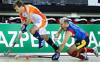 ALMERE - Willem Hertzberger (l) passeert de Spaanse 'vliegende' keep Diego Gavilan Moral, zondag tijdens de wedstrijd tussen Nederland en Spanje om de derde plaats (5-2), tijdens het EK Zaalhockey in Almere.