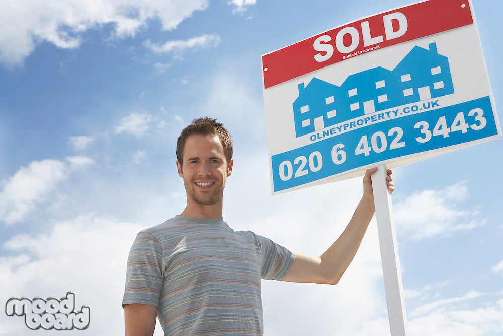 Man holding sold sign against sky