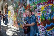 Ein junger Gitarrist spielt für die Besucher der Prager Lennon Mauer (Lennon Wall). Die John-Lennon-Mauer war früher eine gewöhnliche Altstadt-Wand in Prag, aber seit den 1980er Jahren wird sie mit von John Lennon inspirierten Graffiti und Teilen von Beatles-Songtexten bemalt.