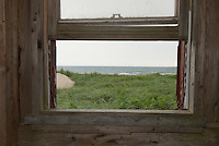 A weathered wood window looks to the ocean at Basinhead, PEI, Canada.