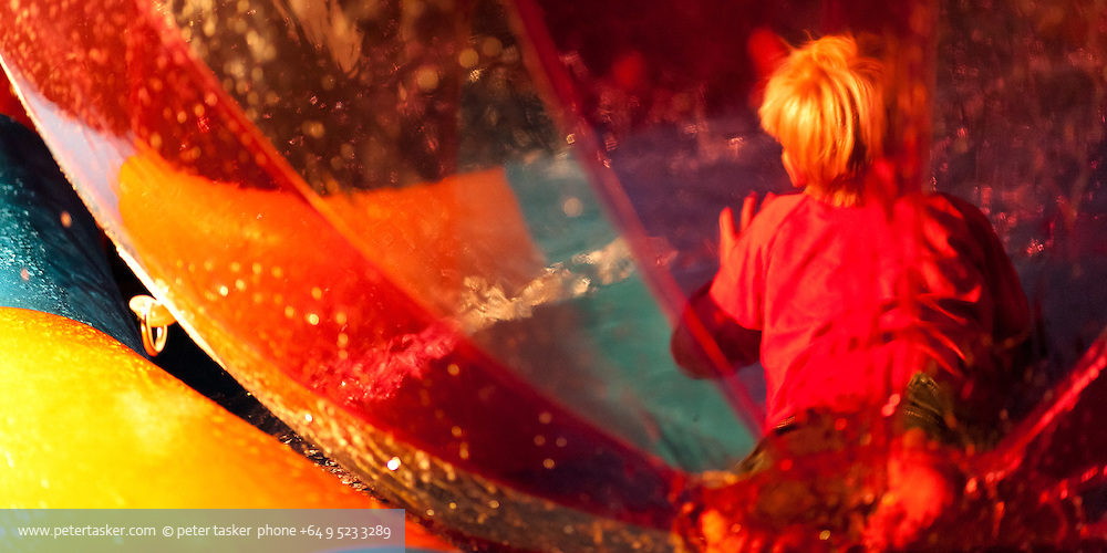 A young boy playing inside an inflated sphere while floating on water at the Auckland 2012 Lantern Festival.