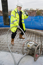 © licensed to London News Pictures. London, UK 25/11/2013. Mayor of London, Boris Johnson helps building an affordable house by filling a hole with concrete in Greenwich Square during a photo call before giving a speech on tackling London's housing needs on Monday, November 25, 2013. Photo credit: Tolga Akmen/LNP