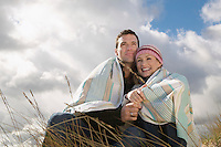 Couple wrapped in blanket embracing in grass