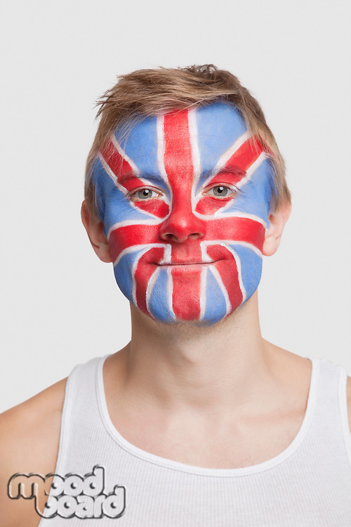 Portrait of young Caucasian man with British flag painted on face against white background