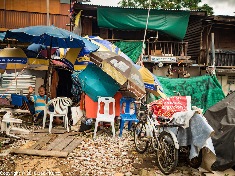 20 SEPTEMBER 2016 - BANGKOK, THAILAND:  A man waves from his home, a lean to built out of beach umbrellas, on the grounds of Wat Kalayanamit. One year after 54 families were forcibly evicted the grounds around Wat Kalayanamit are still undeveloped. Fifty-four homes around Wat Kalayanamit, a historic Buddhist temple on the Chao Phraya River in the Thonburi section of Bangkok, were razed and the residents evicted to make way for new development at the temple. The abbot of the temple said he evicted the residents, who lived on the temple grounds for generations, because their homes were unsafe and because he wants to improve the temple grounds. The evictions are a part of a Bangkok trend, especially along the Chao Phraya River and BTS light rail lines. Low income people are being evicted from their long time homes to make way for urban renewal.           PHOTO BY JACK KURTZ