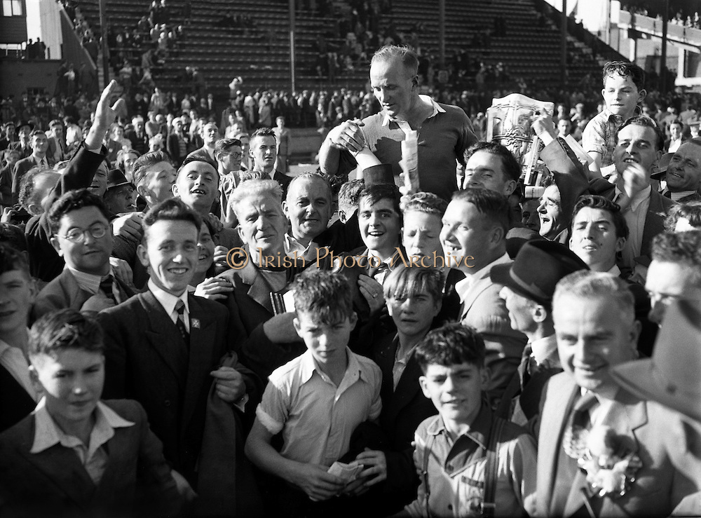 Senior All Ireland Hurling Final - Cork vs. Galway in Croke Park, Dublin. Christy Ring (in air).06/09/1953..Nicholas Christopher Michael Ring (12 October 1920- 2 March 1979), better known as Christy Ring, was a famous Irish sportsperson. He played hurling with the Glen Rovers club from 1941 until 1967 and was a member of the Cork senior inter-county team from 1939 until 1963. Ring is widely regarded as one of the greatest hurlers in the history of the game. Many former players, commentators and fans rate him as the number one player of all-time..In a game as mythologised as hurling, Ring's universally accepted pre-eminence is remarkable. Yet, he possessed everything from talent and ferocious application to longevity and a string of records. Obsessive about the game, he worked relentlessly to sustain a formidable array of techniques, complemented by great vision and anticipation. A shamanistic sense of his own distinctness added to a reputation for eccentricity, but Ring's greatness, coupled with his physical resilience and resourcefulness, also demoralised opponents...Ring has also been the recipient of many awards and honours off the field. In 1959 at the age of thirty-nine his hurling prowess earned him the prestigious Caltex Hurler of the Year award. He was posthumously honoured in 1984 when he was named, by popular opinion, in the right wing-forward position on the GAA Hurling Team of the Century. He was named in the same position on the GAA Hurling Team of the Millennium in 2000...As Ring was walking past the Cork College of Commerce on Morrisson's Island on 2 March 1979 he suffered a massive heart attack and collapsed. He was taken by ambulance to the South Infirmary Hospital but was pronounced dead on arrival. He was fifty eight years-old. The news of his death came as a great shock to the people of Ireland, and particularly to the people of Cork. His funeral was one of the biggest ever seen in Cork with up to 60,000 people lining the streets.....
