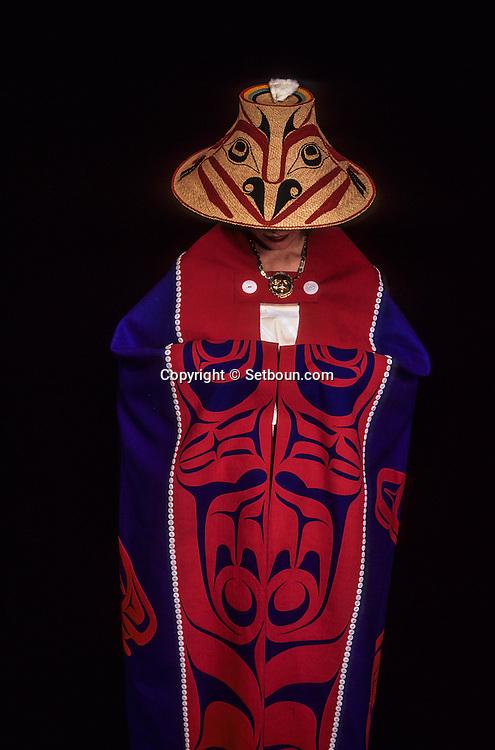 Canada. Vancouver .Traditional  - Haida -  indian dress    Canada   /  Vetement de fête des indiens  - Haida -      Canada Terri-Lynn Davidson modèle une couverture à boutons en laine et suède exécutée par Tracy Auchter de Massett d'après un design de Robert Davidson. La bordure illustre l'Ours Grizzly. Son chapeau traditionnel, tissé en racine d'épinette, et décoré d'un motif de chèvre de montagne peint par Robert Davidson, est l'oeuvre d'Isabelle de Massett. Le sommet est décoré d'un arc-en-ciel peint au centre duquel émerge une peau d'hermine.